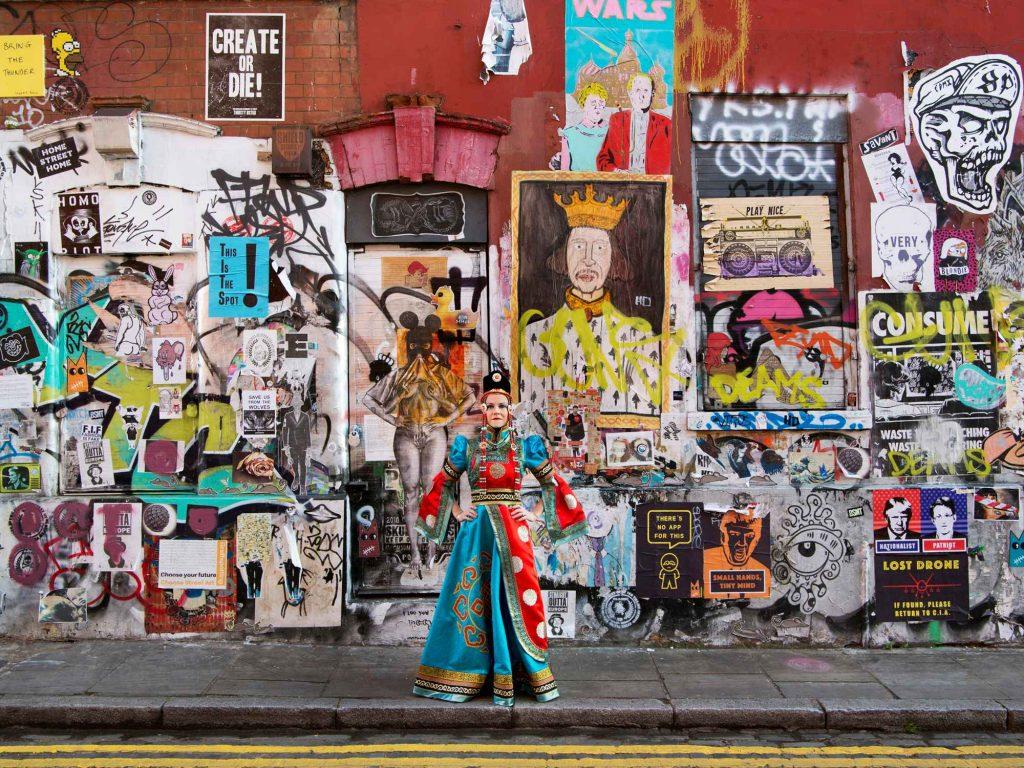 Hilary LANCASTER  Ce portrait me représente telle une «guerrière Urbaine Spirituelle» ; comme quelqu'un qui embrasse les qualités de cou- rage, de force et d'intégrité.J'apporte cette même intégrité et profondeur à mon travail. Lorsque cela s'unit à mon énergie et à ma créativité, nos projets de conception génèrent des intérieurs inspirants et uniques, significatifs et originaux.Ce collage d'art brut de rue à Shoreditch, à l'est de Londres, est provocateur, dynamique et impactant. Ces multiples couches de couleurs et de messages peuvent représenter certains aspects de moi. Le royal et traditionnel costume Mongol que je porte m'impose de régner sur ce 'Queendom' de vérité et de liberté créative, et en inspirer les autres à trouver le leur.  Photo : F Ducout